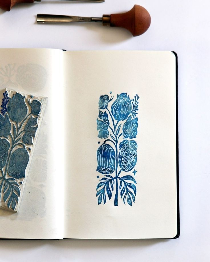 hand carved stamp and it's print blue ink on w…