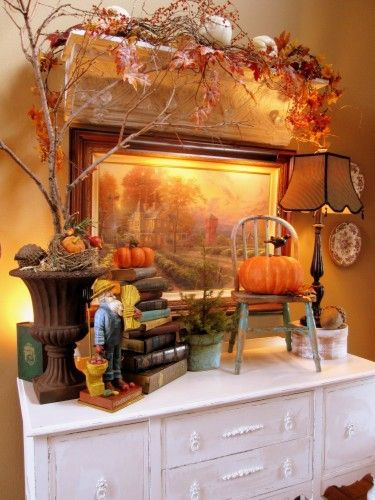 Entry decor.  Love the distressed doll chair with pumpkin/crow on top.  I want this cozy house and all the decor!
