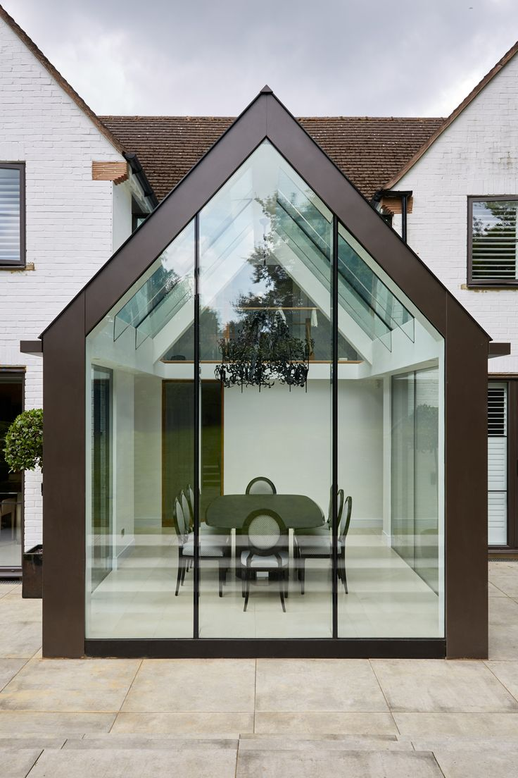 Contemporary mono pitched structurally glazed roof dining room with bronze cladding, laminated glass beams and frameless glass gable wall