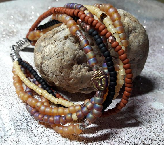 Bohemian bracelet six rows of Brown glazed, ecru and black beads and hematitie bead Buddha gold. Silver lobster clasp and silver metal beads. -length 20 cm