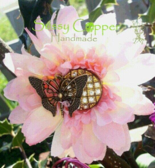 Flor con mariposa. En Broche o horquilla.   Derechos de imagen y creacion de piezas de Sussy Copper. sussycopper@gmail.com