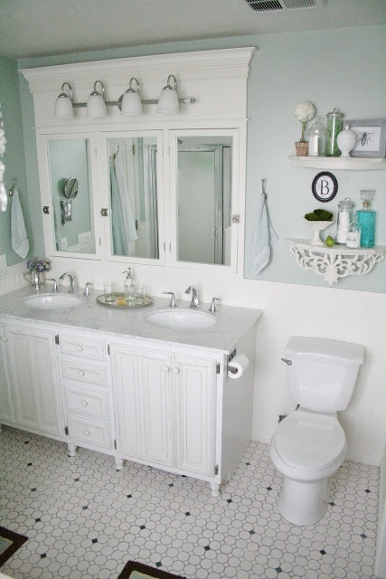Love the blue wall color & half rnd shelves above the commode.