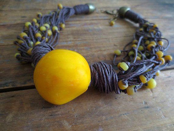 This necklace is made of yellow free form tagua nut ( 30mm x 35 mm), Indo-Pacific hand made glass beads and dark brown linen cord. Length of the