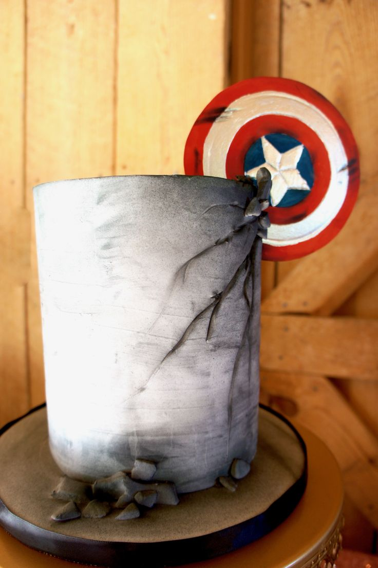 Captain America grooms cake. The infamous shield crashing into the triple barrel cake made to look like cement. #redvelvet