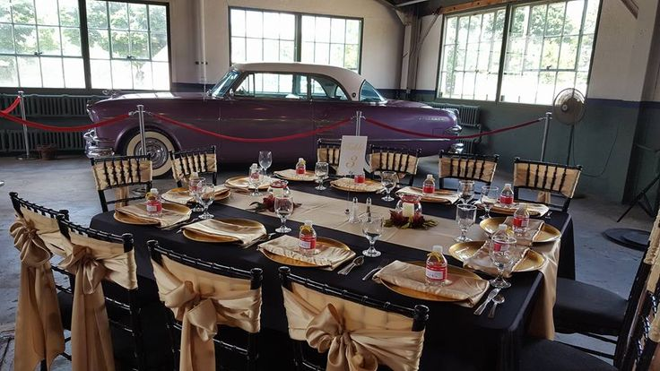 Elegant guest table in the Repair Garage building at the Packard Proving Grounds Historic Site in Shelby Twp, Michigan. Amethyst hard top packard classic car. Black and gold wedding. Chivari chairs. Water bottle favor