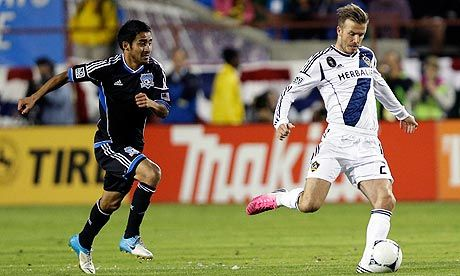 Los Angeles Galaxy's David Beckham, right, dribbles past San Jose Earthquakes's Rafael Baca during an MLS playoff game. Photograph: Marcio Jose Sanchez/AP