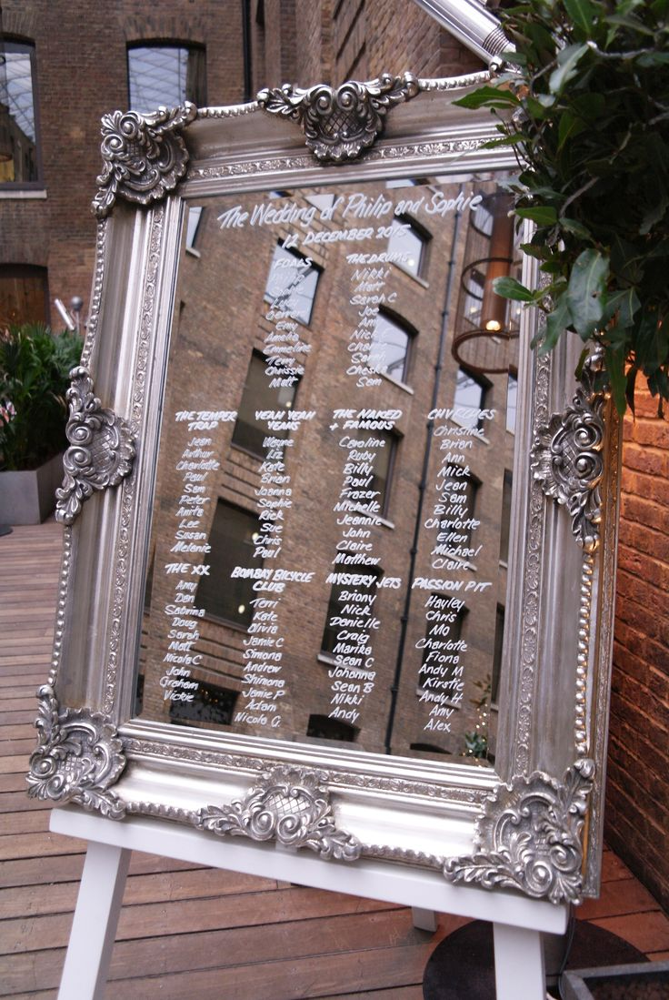 large mirror on white easel with hand written table plan by wwwstressfreehire