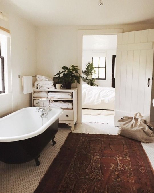 cozy off-white bathroom, black clawfoot tub, hexagon tile floors, antique rug