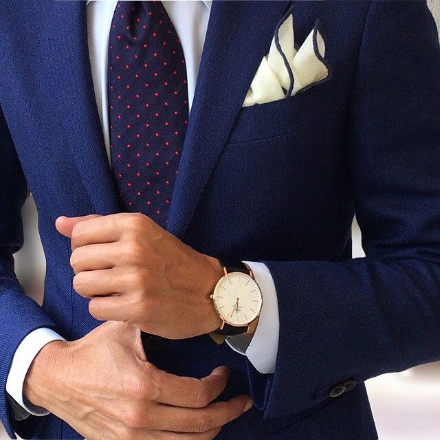 Navy jacket, white shirt, navy tie with red pin dots