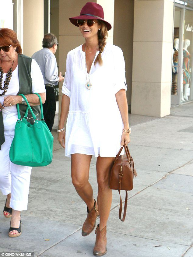 Golden girl: The 34-year-old revealed her long and tanned legs in the short frock