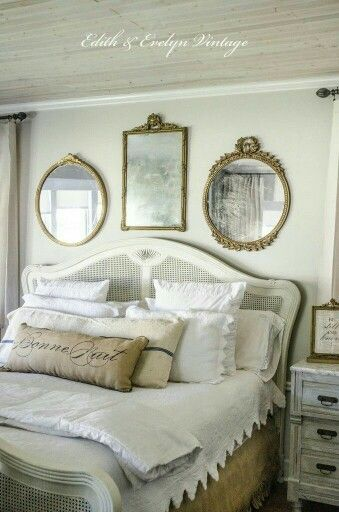 Collection of antique mirrors and layers of neutral colored linens.  Romantic touches and a variety of textures make for an inviting bedroom.