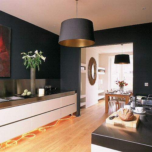 Modern black kitchen: Farrow & Ball's 'Off-Black' Walls painted Farrow and Ball's Off-Black are warmed by honey-colored wood floors and chic white units by Diana MacGregor at Harvey Jones. Bespoke black lampshades from Max Watt of Norwich link the kitchen and dining areas. Photo from housetohome.co.uk.
