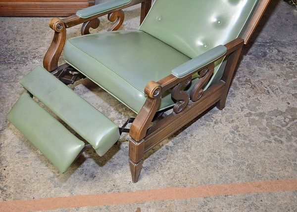 $75 July 2016. A Mid Century Modern green vinyl recliner chair. This chair features a rectangular back with button tufting, framed by a mahogany finish wood; wood fame continues to arm with elbow pads and scrolling to the end of arm rest with s-scroll arm supports atop incised side slats. Front legs are geometric and tapered to a pointed foot. Seat reclines with a two-part footrest.