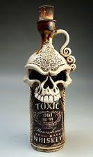 "Toxic Moonshine Whiskey Bottle""  The first cup or so of moonshine in a batch is where the impurities (such as the poisonous methanol alcohol) gather. Responsible distillers will toss this away,. However some  have been known to include bizarre ingredients including manure and embalming fluid. This one-of-a-kind handmade bottle was made for those kinds of bad batches and is clearly labeled to warn those who dare to drink it"
