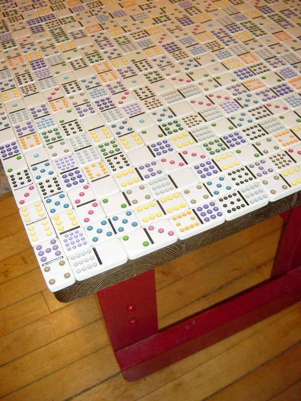 Domino covered table top. Any flat game pieces would work. I like the idea of a scrabble game top.