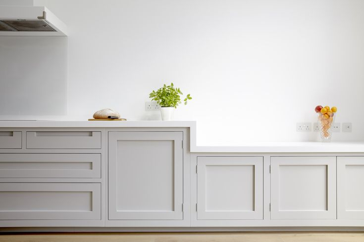 A clean and crisp handleless shaker design with Corian worktops.