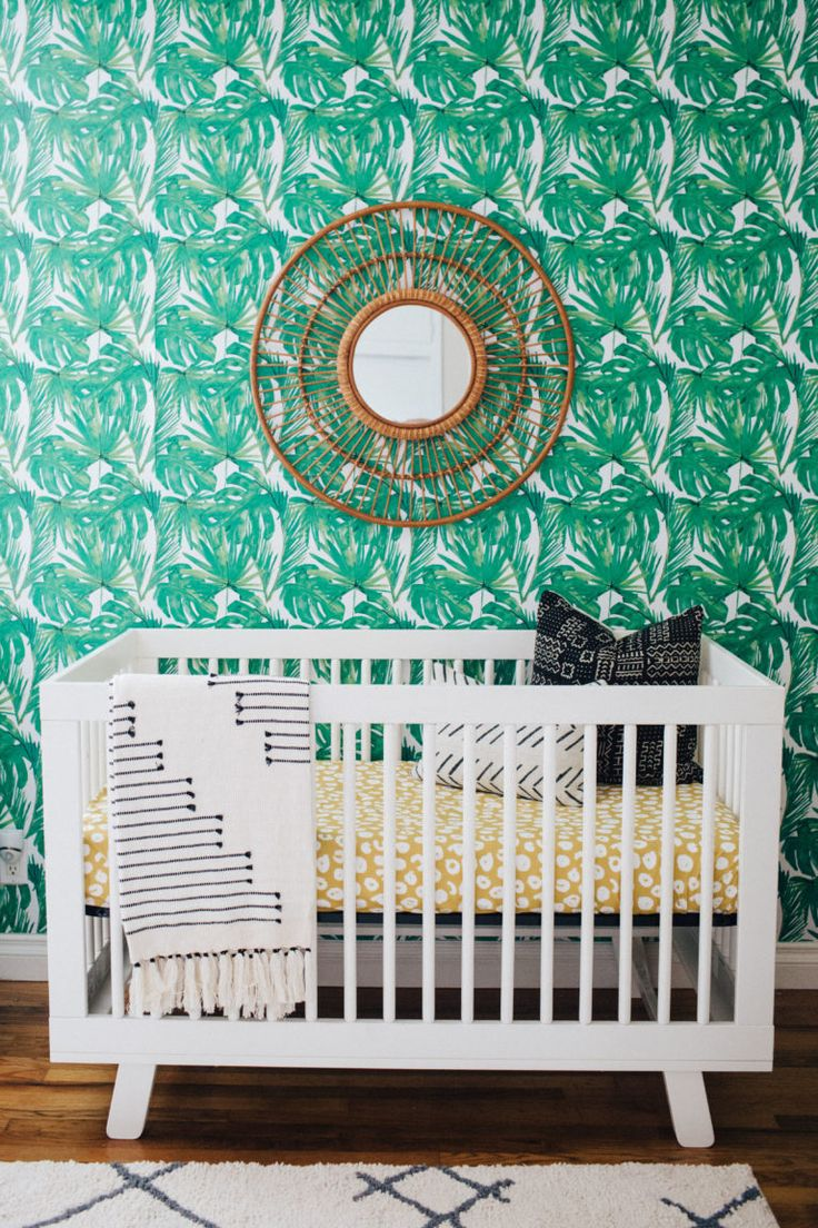 This palm tree wallpaper is so chic in this shared gender neutral nursery!