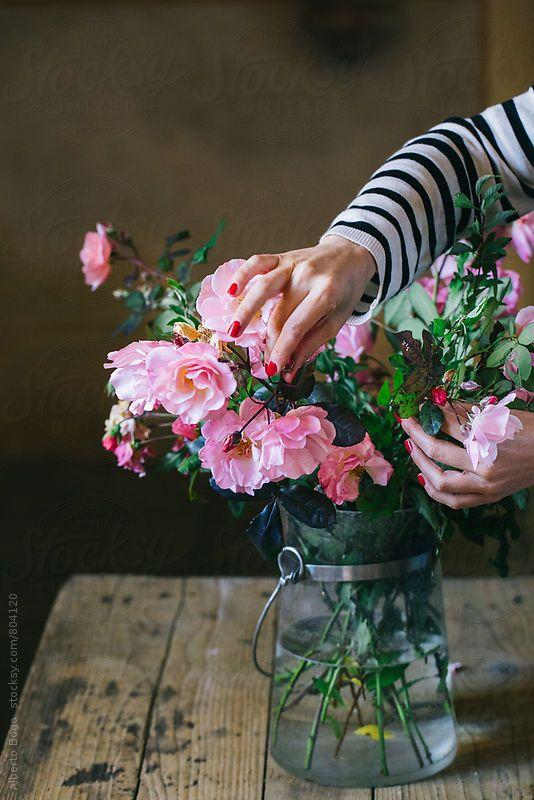 Woman arranging fresh roses. Alberto Bogo for Stocksy United