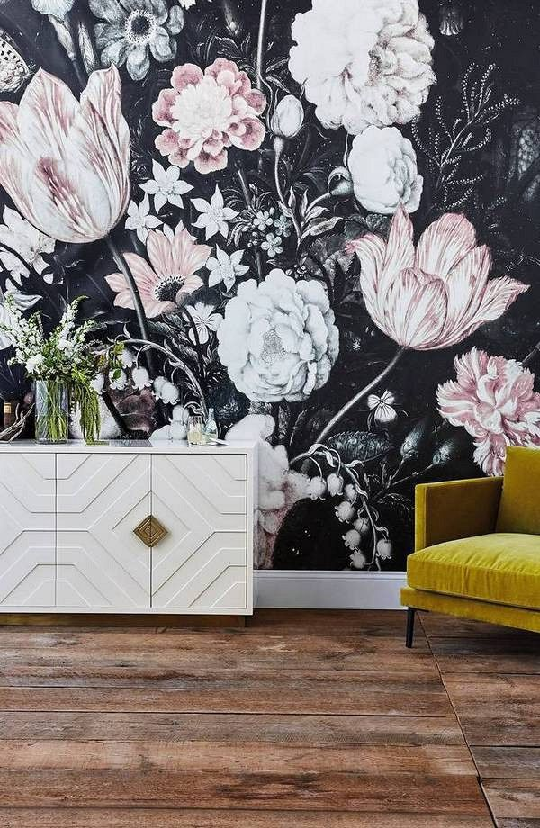 Living space with a stormy floral print wallpaper, a white credenza and a yellow velvet armchair