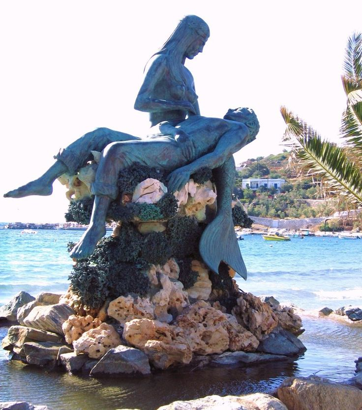 Mermaid Statue in Greece. Mermaids were often depicted as saving sailors from the sea. Here this is beautiful portrayed and makes one ponder whether this scene was actually a picture in reality.
