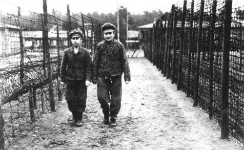 Kotälla (l) waarnemend kampcommandant, gevangen in 'De Rozentuin' in kamp Amersfoort. In de Rozentuin moesten gevangenen uren/dagen rechtop staan, in een smalle afrastering van prikkeldraad, zonder eten/drinken in weer/wind. Gevangenen die omvielen werden met stokslagen weer overeind gejaagd. Kotälla is een van de beruchtste kampbeulen van Amersfoort. In 1948 werd hij ter dood veroordeeld, later omgezet in levenslang. Hij stierf in 1979. Foto: Amersfoort 3 maart 1944.