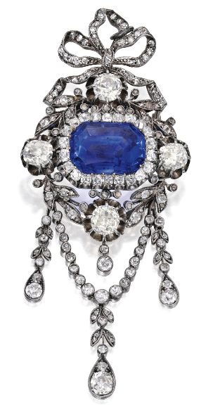 Gold, Silver, Sapphire and Diamond Brooch. Centring a buff-top emerald-cut sapphire weighing 16.96 carats, within a bow motif frame set with numerous old mine and single-cut diamonds weighing approximately 6.85 carats; circa 1890; together with an 18 karat white gold rope chain for wear as a pendant.