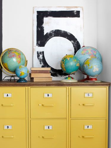 Goodwill filing cabinets spray-painted yellow and topped with plywood.  globes & the #5!