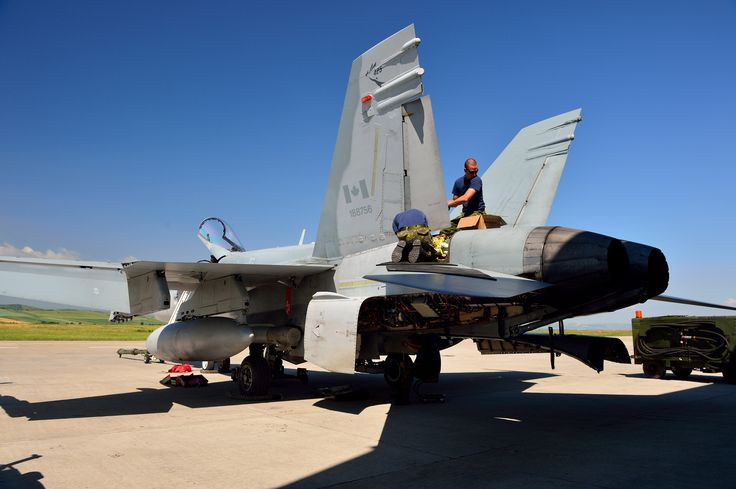 Tail Number (756): Maintenance is performed aboard a CF-18 Hornet on June 11, 2014 in front of Hangar 3 in Câmpia Turzii, Romania where members of Canadian Air task Force Romania are participating in OP REASSURANCE.   Photo by LS Alex Roy, 3 Wing Imaging (BN2014-1026-02)