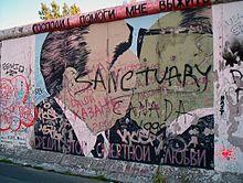 """Sul graffito Leonid Brežnev ed Erich Honecker che si baciano. La scritta in alto, in cirillico dice: """"Signore! Aiutami a sopravvivere a questo amore letale"""" MURO DI BERLINO"""