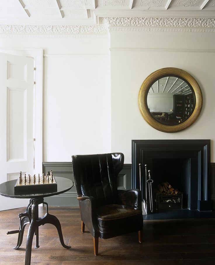 Kent. The timber bolection-profile fireplace in the library is painted in Farrow & Ball's 'Off Black'. Regency giltwood mirror above.
