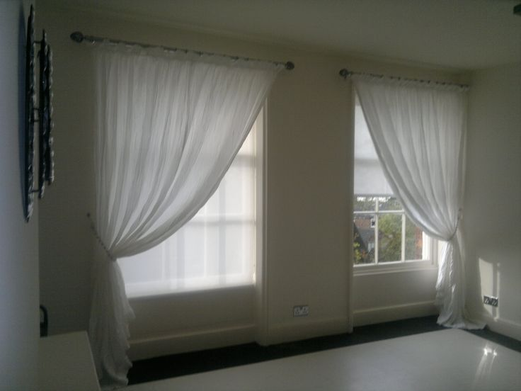Sheer voiles are mounted over functional roller blinds a for Window voiles