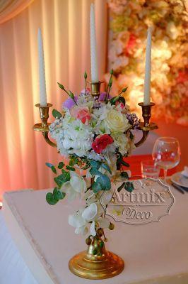 Золотые канделябры с цветочными композициями на свадебном президиуме