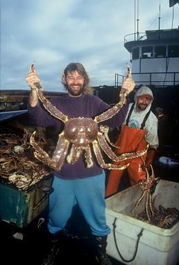 Captain Phil Harris showing off an Alaska King Crab on the deck of his ship the Cornelia Marie