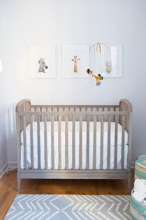 Stunning boy's nursery features a safari animal mobile by Etsy Patricija and baby animal art by The Animal Print Shop placed above a gray stained crib, Land of Nod Archway Crib, dressed in Serena & Lily Pin Dot Crib Sheets facing a gray chevron rug, CB2 Hash Looped Rug.