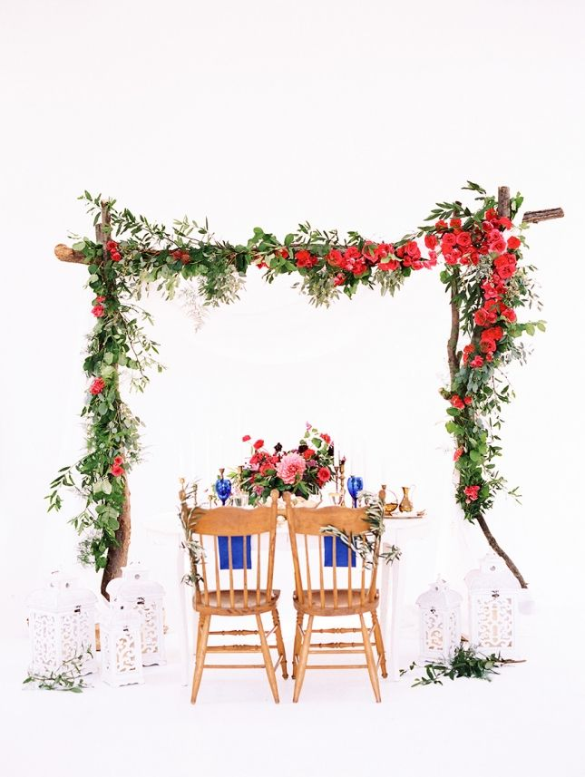 Floral installation with bright blooms above sweetheart table