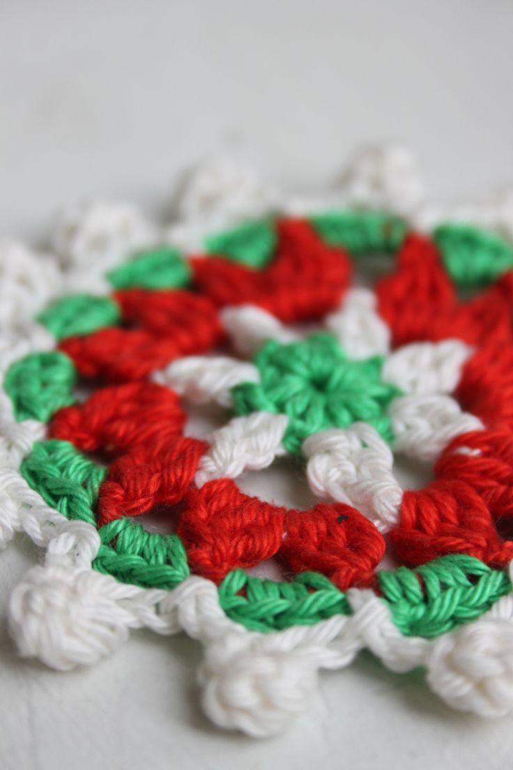 Crochet doily uit inhaken op de feestdagen. Gehaakte onderzetter met bolletjes rand in traditionele kerstkleuren rood, groen en wit