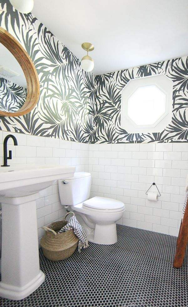 Basement Bathroom Makeover - White pedestal sink with matte black faucet. Round wooden mirror. White subway tile and black penny tile on the floor pairs with bold black and white palm leaf wallpaper. I love the hits of brass. House Of Hipsters
