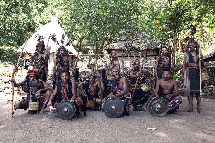 A group of Abui men are posing wearing traditional clothing equipped with the instruments for a dance performance. A gong and a brass drum called moko are significant music instruments to accompany the traditional rhyme in a dance performance.