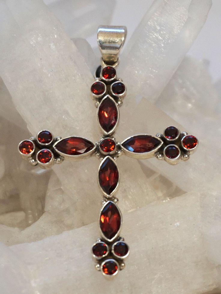 """5 Marquis-cut faceted Garnet gemstones, accented with 13 round faceted garnets, bezel-set in 925-hallmarked sterling silver. Length: 2.25"""" with bail. Width: 1.5"""""""