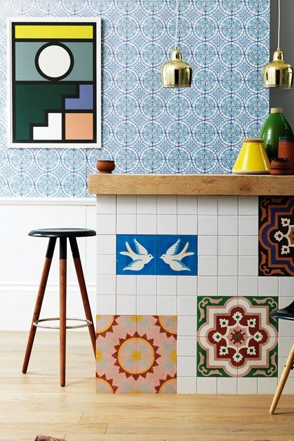 Create a retro-inspired kitchen by layering geometric tiles with bold colour. Simple brass pendant lights and black chairs allow the eye to rest; letting the vibrant elements shin