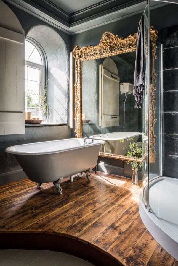 Glamorous bathroom with rustic wood floors, gold mirror, clawfoot tub