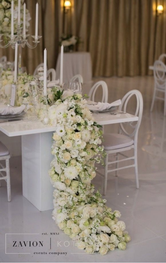 What a gorgeous wedding table, wit huge white floral mass arrangements, white flowers, mirror and white vases, orchids, roses, clear glass vases, royal wedding, best wedding day, best wedding ever, floral runner, white flower runner orchid runner
