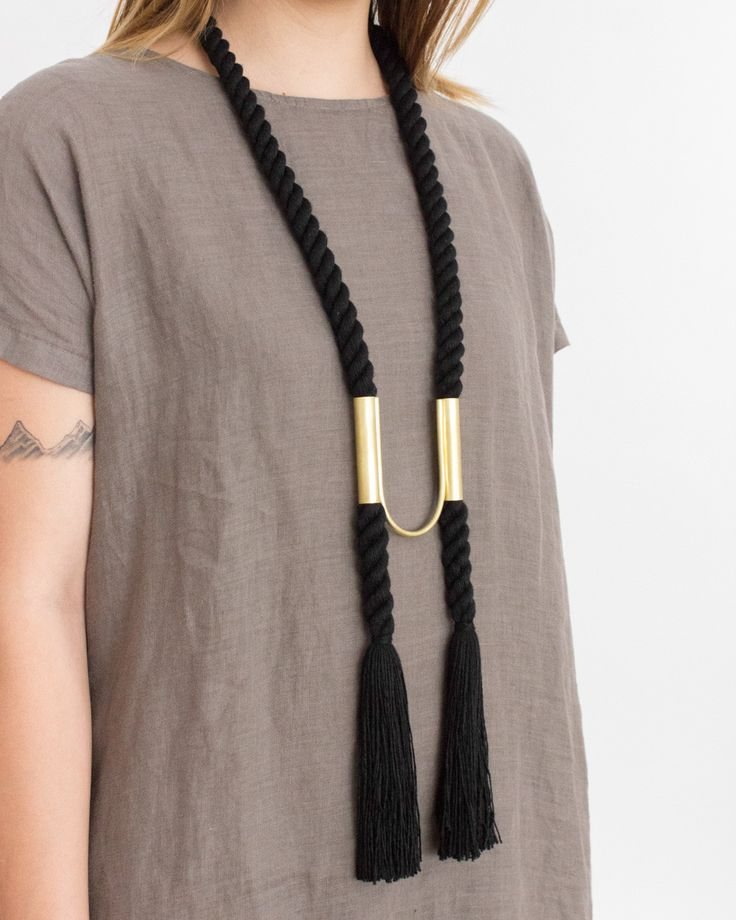 The Compass Necklace is made with hand-spun rope and 100% raw brass tubing. The brass body is cut, bent, and soldered by hand and can be adjusted to any position on the rope. For a bolo necklace look,