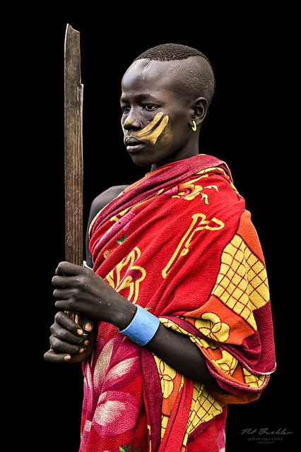 """Young Warrior from the Karo Tribe, South Omo Valley, Ethiopia.  This picture is part of a Serie called """"African Vogue"""", which was taken in October 2013.   All pictures were taken in natural light situations – no flash was used. In a few cases, a sun swapper or a shade panel was used but mostly, pictures were taken in direct sun light / clouds and natural shade situations. Most of the portraits were taken """"on the field"""", which means that people did not prepare themselves for the shooting –…"""