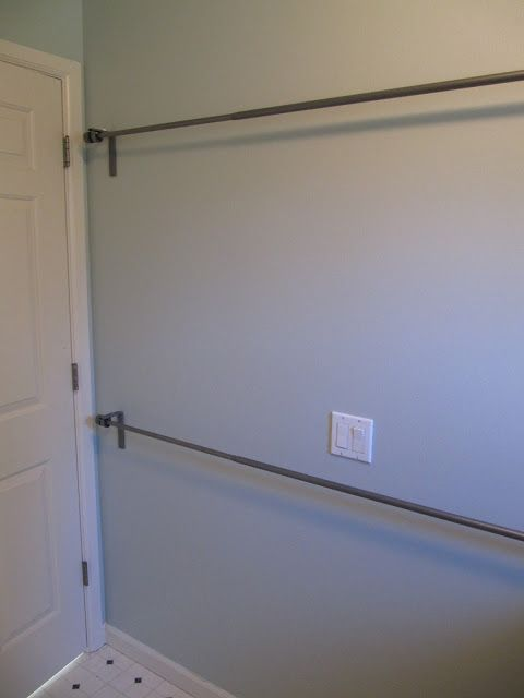 curtain rods hung on the laundry room wall to hand dry clothes