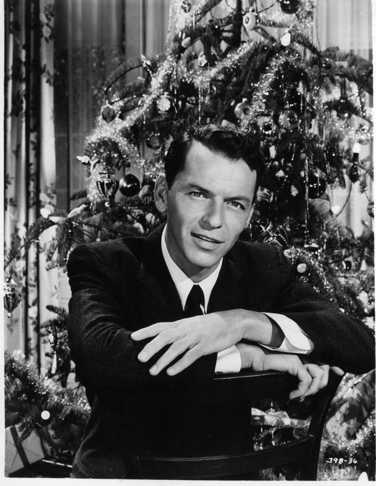 Frank Sinatra sits in front of a Christmas tree in a scene from the film Young At Heart.