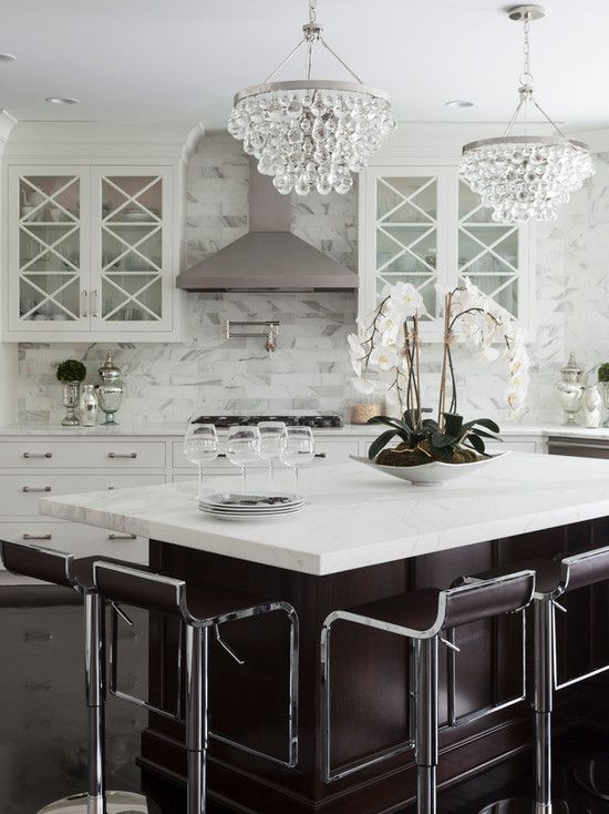 source: Susan Glick Interiors  Beautiful kitchen features glass-front cabinets and white lower cabinets paired with calcutta marble countertops and calcutta marble subway tile backsplash. Kitchen with Robert Abbey Bling Chandelier over angled kitchen island with calcutta marble top lined with leather piston stools over dark wood floors.