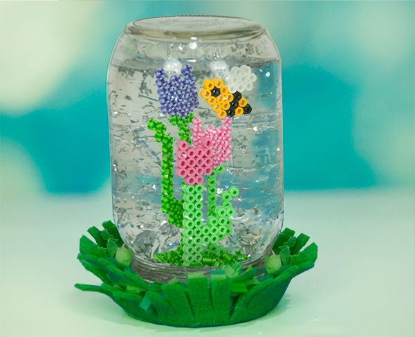 """Make your own """"no-snow"""" globe when you use glitter instead to float around the pretty garden flowers. The project is easily created with a simple mason jar, and you can use this same technique with other designs that fit inside the jar."""