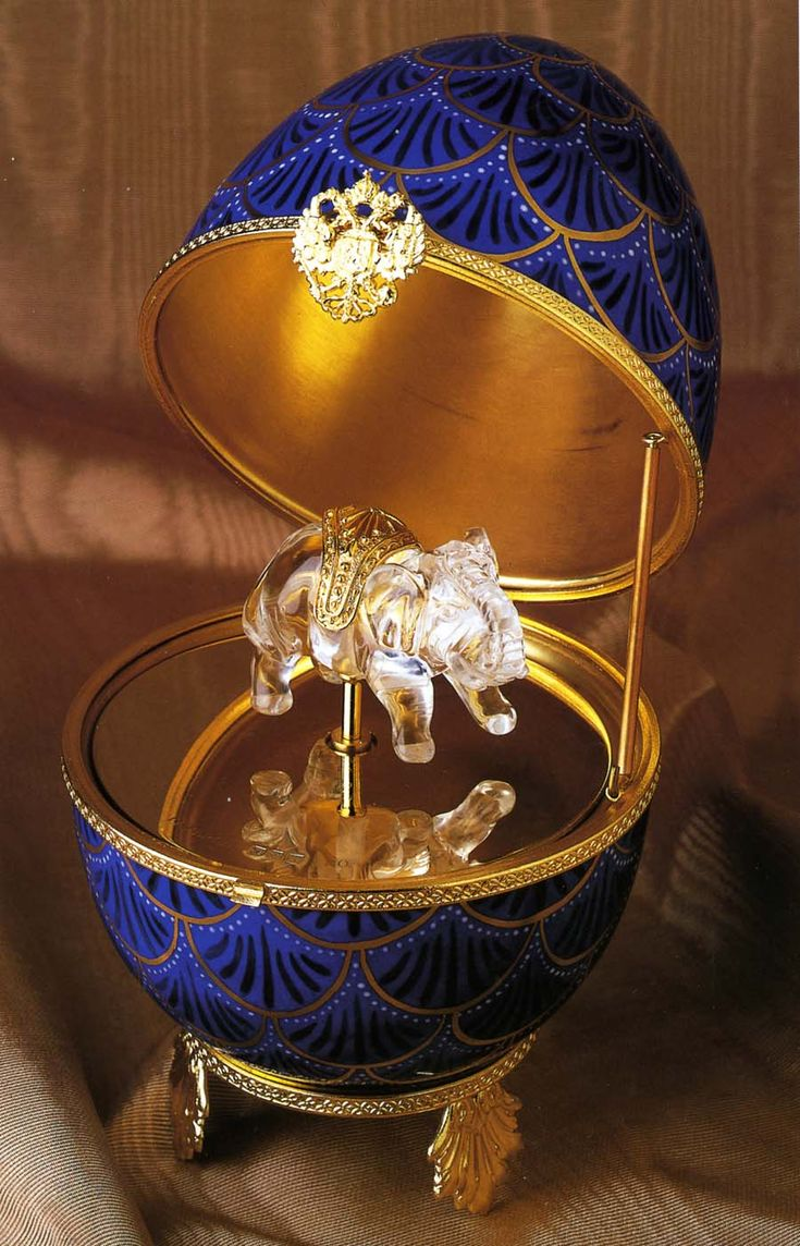 "Faberge Egg: Imperial Pine Cone Musical Egg / A hand-painted Limoges porcelain Faberge Egg with a hand-carved rock crystal elephant surprise that gently rotates as the Swiss-made musical movement plays ""Magic Flute"". Limited Edition. Height 7""."