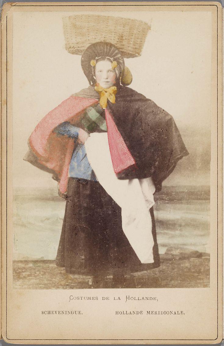 Vrouw in Scheveningse klederdracht; negotiante (visverkoopster) met vishoed en vismand; zij draagt een rood gevoerde schoudermantel, een wit schort dat omgeslagen gedragen wordt waardoor de rok is te zien, een lang gebloemd katoenen jak, een geplooide muts met ijzer en gouden boeken. Uit een voor de Franse toeristenmarkt gemaakte leporello met 12 met de hand ingekleurde kabinetfoto's van Nederlandse streekdrachten. 1875-1885 fotograaf: A. Jager #ZuidHolland #Scheveningen